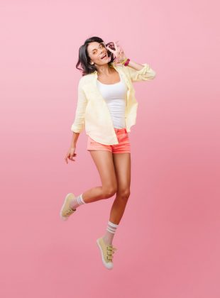 Fascinating hipster girl in yellow outfit spending time in studio with pink walls. Romantic hispanic lady in stylish sneakers dancing with pleasure.